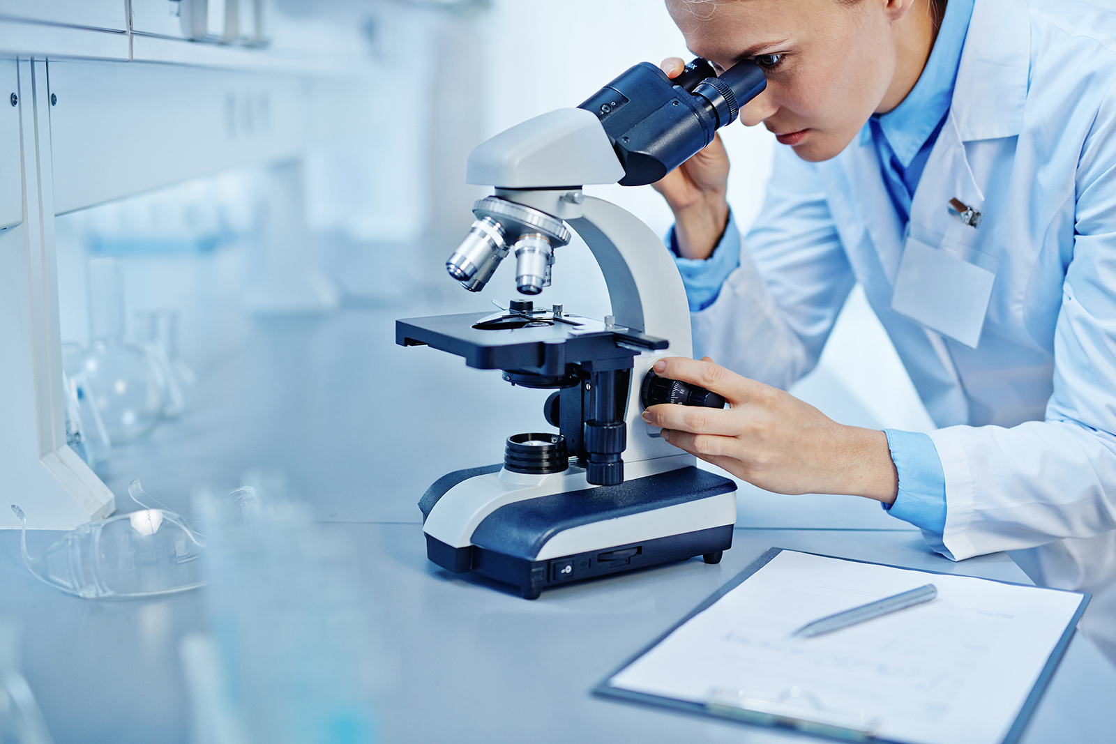 scientist in a lab using a microscope and looking at a slide