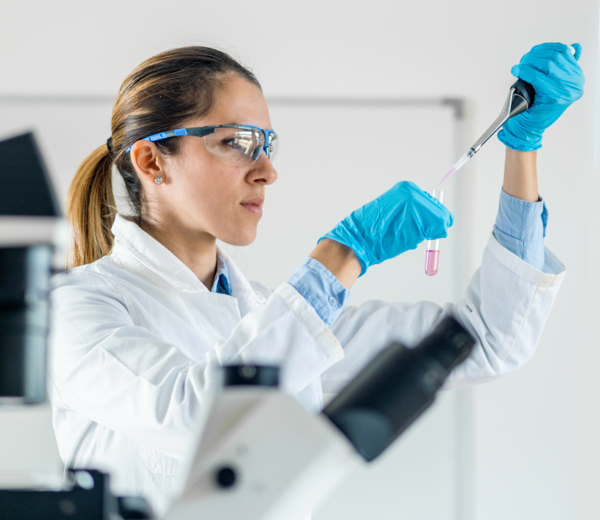 scientist working in a lab with safety goggles on and working with glass test tube
